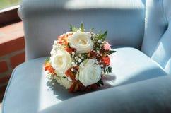在软的古色古香的椅子的新娘花束 免版税库存图片