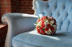 在软的古色古香的椅子的新娘花束 库存图片