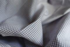 在软的折叠的灰色方格的织品 库存图片