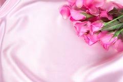 在软的桃红色丝织物,罗马的花束甜桃红色玫瑰花瓣 免版税图库摄影