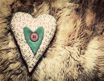 在软的毯子的葡萄酒手工制造长毛绒心脏枕头 免版税库存照片
