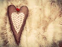 在软的毯子的葡萄酒手工制造长毛绒心脏枕头 库存照片