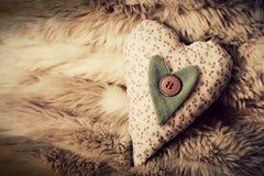 在软的毯子的葡萄酒手工制造长毛绒心脏 库存图片