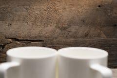 在软的焦点咖啡杯后的木背景 免版税库存图片