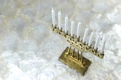 在软的白色背景的小黄铜光明节menorah,有角度的权利 免版税库存图片