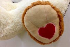 在软的长毛绒玩具脚底缝合的心脏  免版税库存照片