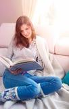 在软绵绵地白色的美丽的女孩阅读书 库存照片