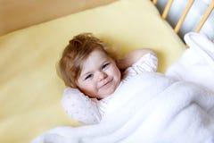 在轻便小床的逗人喜爱的矮小的女婴在睡觉前 愉快的镇静孩子在床上 去的睡眠 平安和微笑的孩子 库存照片