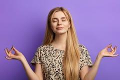 在轻的女衬衫打扮的金发妇女保持眼睛闭上在瑜伽期间 库存图片
