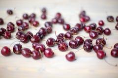 在轻的木桌关闭驱散的甜樱桃很多红色莓果,束在白色背景的成熟樱桃莓果 免版税库存图片