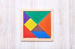 在轻的木背景的一个七巧板难题 免版税图库摄影