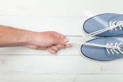 在轻的木背景的时兴的鞋子,手在鞋带拉扯 免版税库存照片