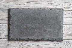 在轻的木背景的灰色具体牌 库存图片