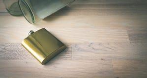 在轻的木背景的金黄金属烧瓶与可看见空的玻璃瓶 库存图片