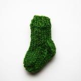 在轻的背景的一只小,手工编织的羊毛袜子 免版税库存图片