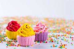在轻的背景的三块微型多彩多姿的糖杯形蛋糕 库存图片