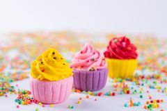 在轻的背景的三块微型多彩多姿的糖杯形蛋糕 库存照片