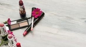 在轻的背景的不同的化妆产品 与化妆用品混合的紫罗兰色花 免版税库存照片