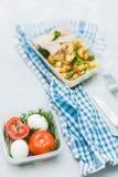 在轻的背景的可口和健康食物 成熟蕃茄,在容器的被剥皮的鸡蛋 免版税库存照片