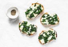在轻的背景,顶视图的无盐干酪乳酪乳脂状的菠菜bruschetta 可口健康早餐,快餐,开胃菜 库存照片