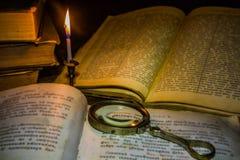 在轻的蜡烛下的旧书和放大器玻璃 免版税图库摄影