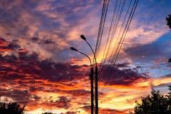 在输电线背景的明亮的美好的日落  图库摄影