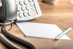 在输送路线电话旁边写作说谎在空白的白色短信卡 免版税库存图片