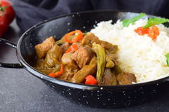 在辣咖喱sause的猪肉用茄子和青豆,供食用在一个黑金属碗的煮熟的米在灰色 免版税库存图片