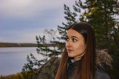 在边的女孩神色以森林湖为背景 免版税库存图片