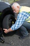 在边缘的年迈的人改变的漏的轮胎 免版税图库摄影