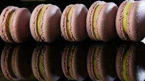 在边缘的特写镜头紫罗兰色法国macarons立场在与反射的行 股票录像