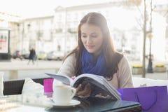 在边路咖啡馆的美丽的妇女阅读书 库存图片