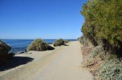 在达娜子线海滩和盐小河之间的公开走的足迹在达讷论点,加利福尼亚靠岸 库存照片