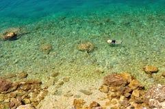 在达尔马希亚多岩石的海滩的看法在有游泳人的克罗地亚 库存图片