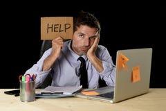 在运作在办公计算机书桌的重音的疲乏的绝望商人拿着标志请求帮忙 库存图片