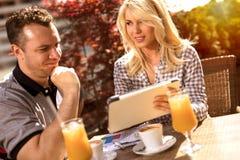 在运作在数字式片剂的咖啡馆的偶然企业夫妇 免版税库存照片