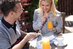在运作在数字式片剂的咖啡馆的偶然企业夫妇 免版税库存图片