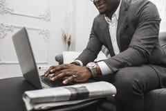 在运作在膝上型计算机后的一套灰色衣服的年轻非裔美国人的商人 库存图片