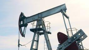 在运作的过程中的作用的油井架 运转的油泵,在背景的抽油装置 股票录像