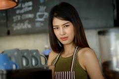 在运作cof的现代时髦咖啡馆的亚洲女性妇女barista 库存图片
