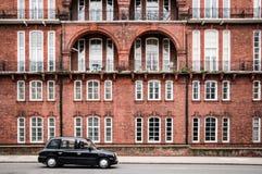 在运动和老大厦的伦敦出租汽车 免版税库存照片