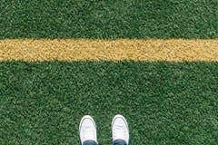 在运动场与两双鞋子,个人p的人为草皮草 库存图片
