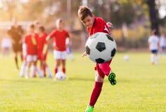 在运动场的男孩踢的橄榄球 免版税库存照片