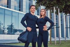 在运动服、性感的白肤金发的女孩和一个英俊的肌肉人的愉快的健身夫妇在现代城市站立反对a 库存照片