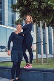 在运动服、性感的白肤金发的女孩和一个英俊的肌肉人的愉快的健身夫妇在现代城市站立反对a 免版税库存照片