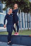 在运动服、性感的白肤金发的女孩和一个英俊的肌肉人的愉快的健身夫妇在现代城市站立反对a 免版税库存图片
