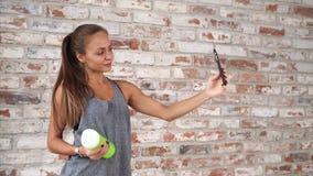 在运动服打扮的女孩由电话采取selfie在健身房的砖墙附近 影视素材