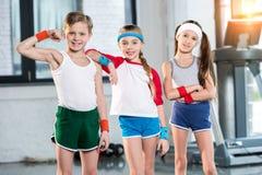 在运动服的可爱的孩子微笑和摆在健身演播室的 免版税图库摄影