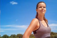 在运动服的少妇portriat在夏天smili的蓝天 免版税库存照片