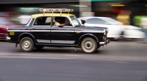 在运动的老传统黑和黄色出租汽车在孟买,印度 免版税库存图片